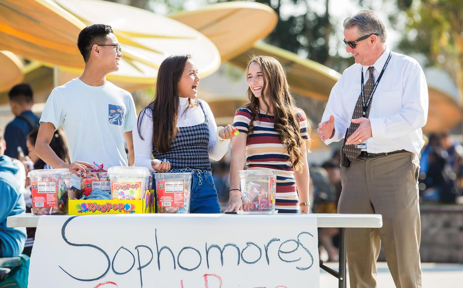 Administrator buying snacks from students at outdoor student store.