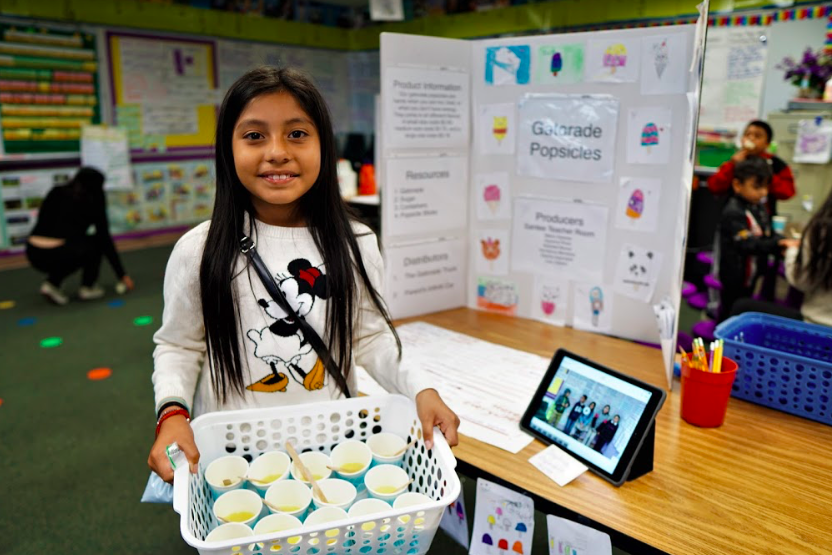 student holds basket of drinks for her project