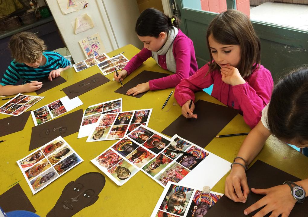 A boy with wavy light brown hair wearing a turquoise and navy blue striped shirt, and three girls with dark brown hair, two in pink shirts and one in white, sit at a yellow table drawing portraits on black paper using photos of people in different African tribal dress as models.