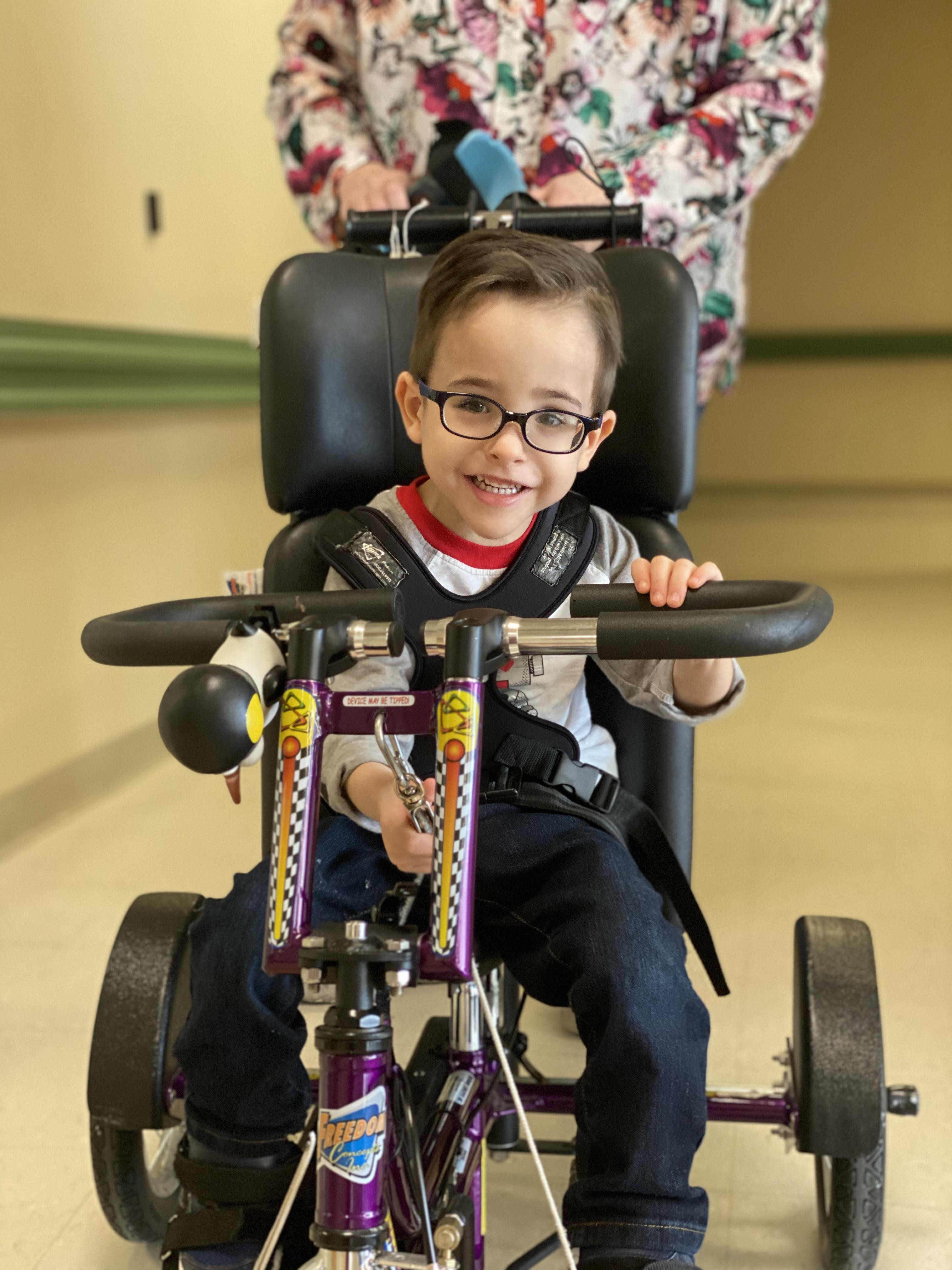 Student in the Primary Program bike riding during an Occupational Therapy exercise.