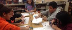 Students at desk using tweezers to explore owl pellets