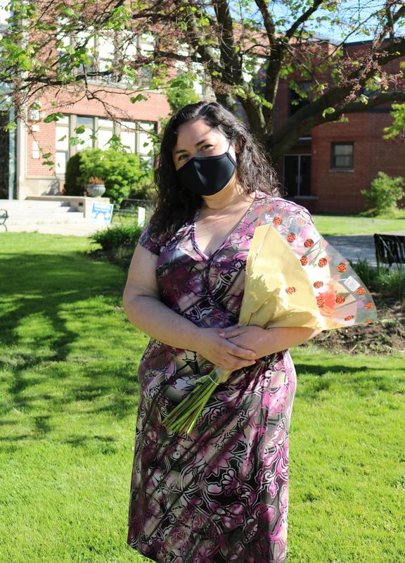 Photo of Nicole Scimone holding bouquet of flowers outside