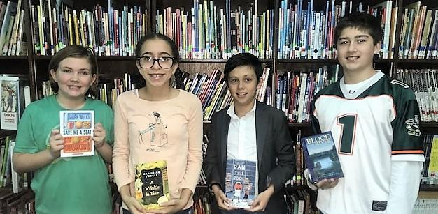 4 students holding books in front of bookshelf