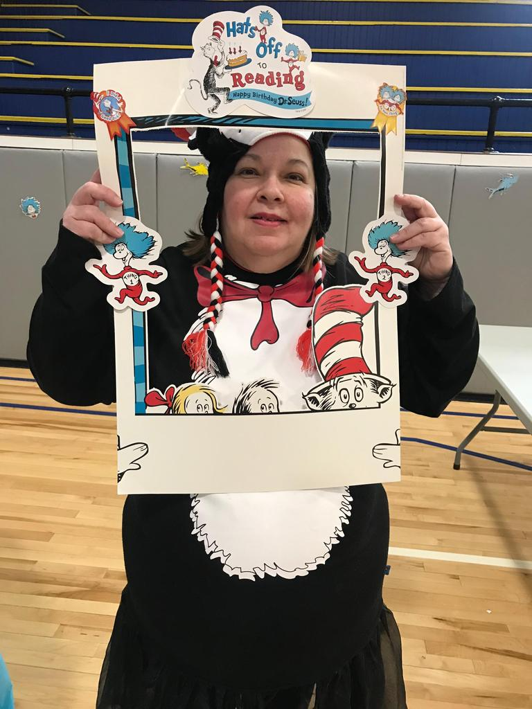 parent liaison kanick dressed as the cat in the hat with a cut out picture from of hats off to reading