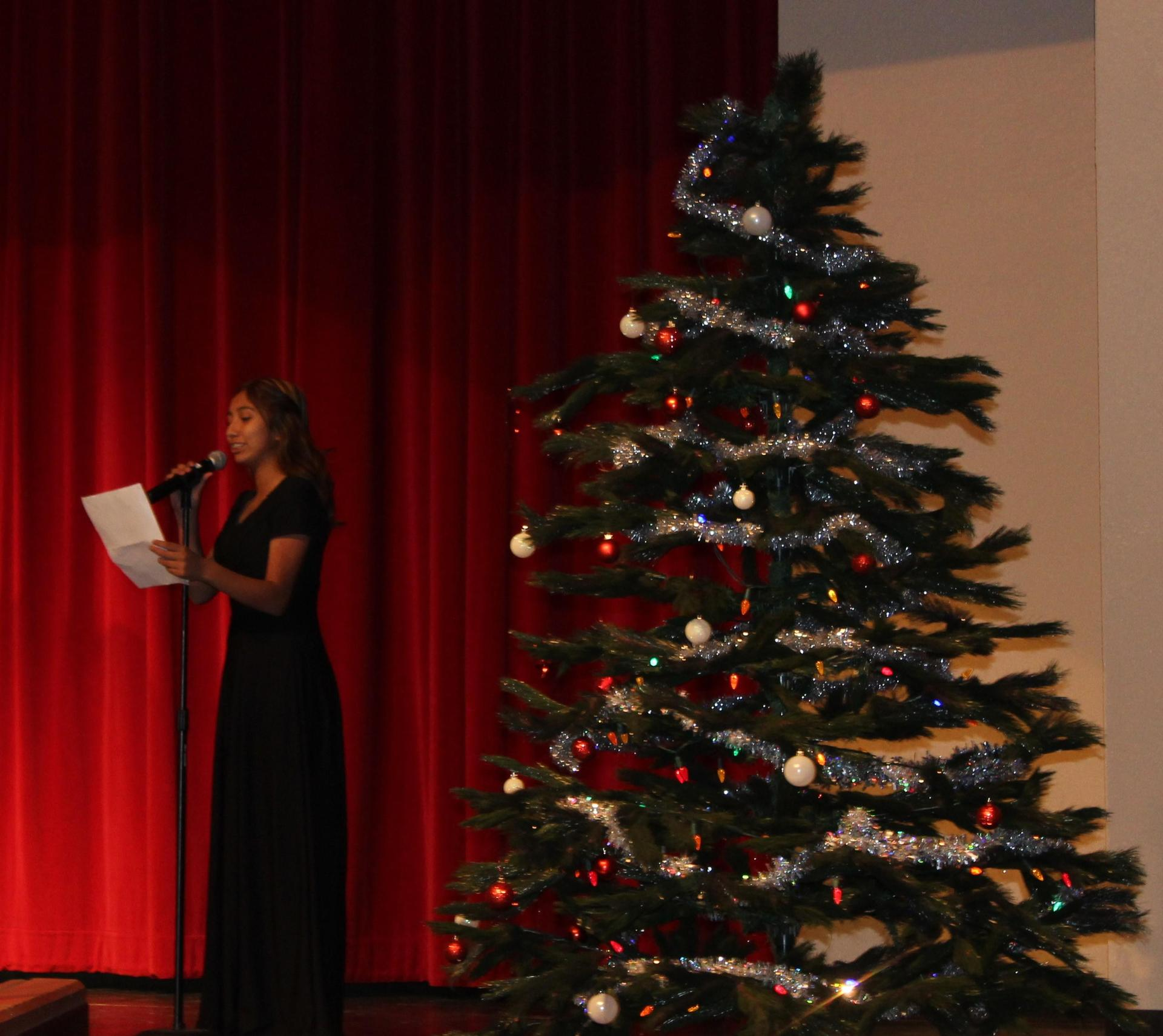 Sophia Atilano reads near the Christmas Tree.