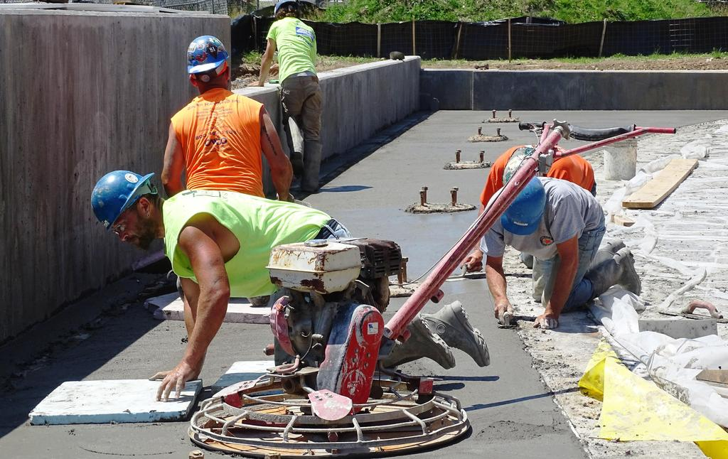 Constructing the concrete foundation for the large group instruction room is a labor-intensive process. Pictured in this snapshot are five members of general construction company Bast Hatfield's concrete construction crew on July 8, 2019 working diligently to smooth freshly poured cement at the job site.
