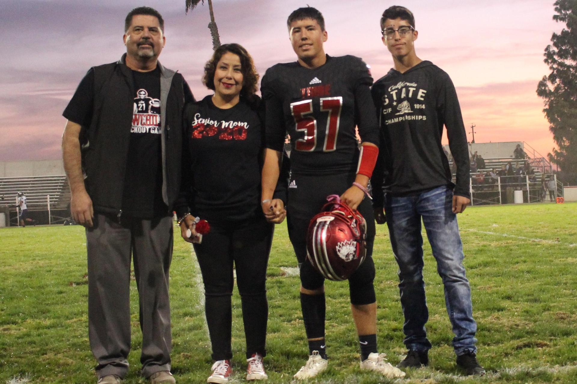 Senior football player Roman Diaz and his escorts.