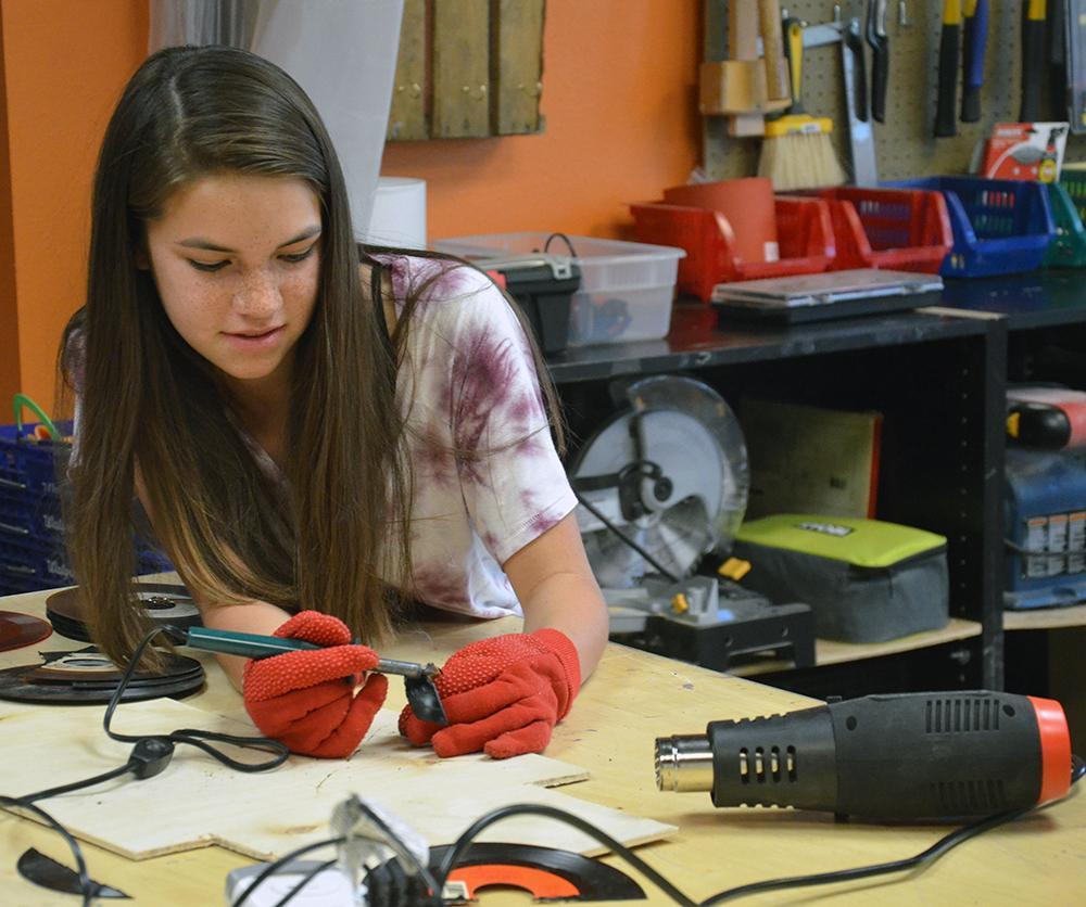 Girl uses soldering gun in makerspace