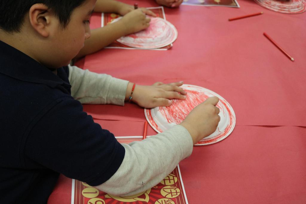 kids  coloring their paper plates with red crayon