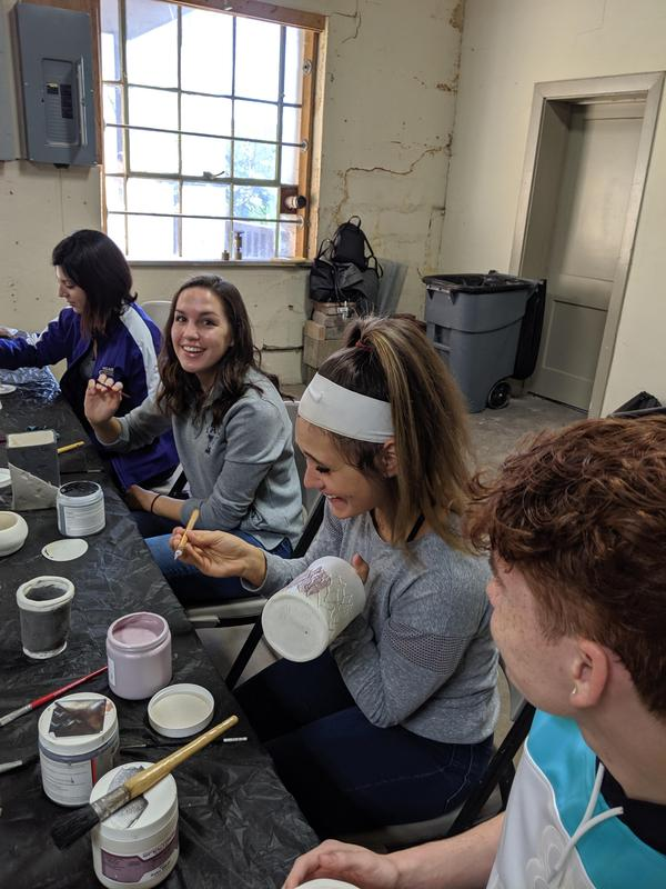 photo of students painting pottery
