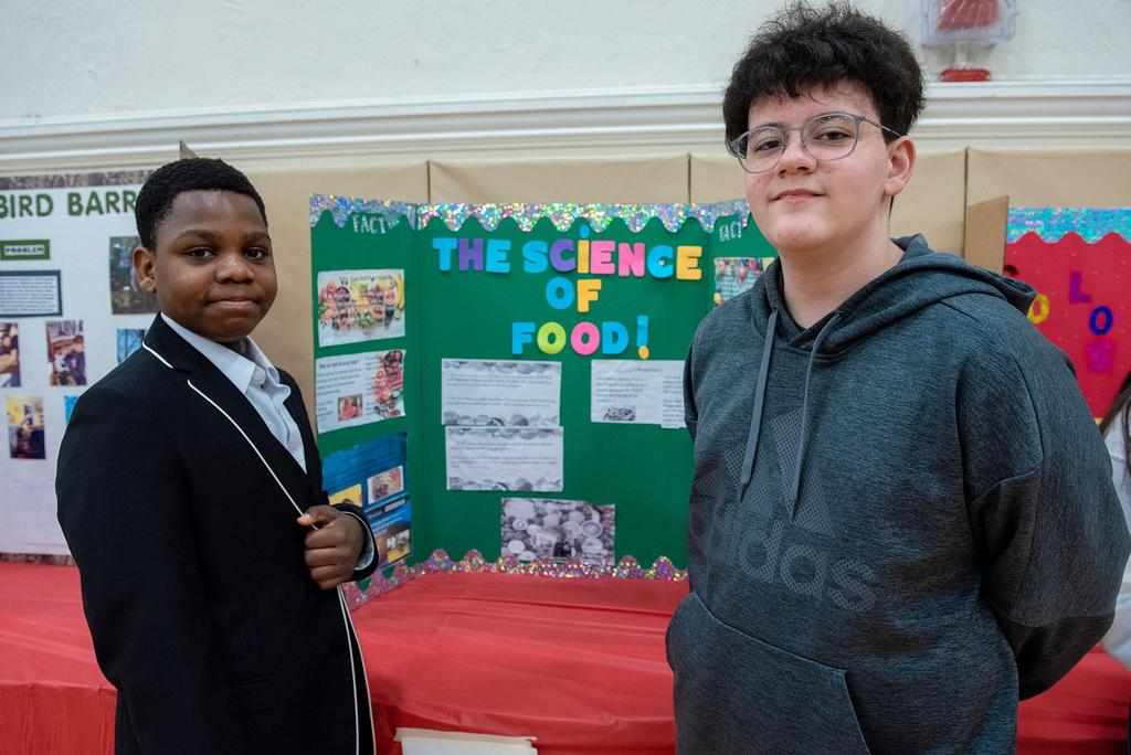 Posed photo of two students in front of their project