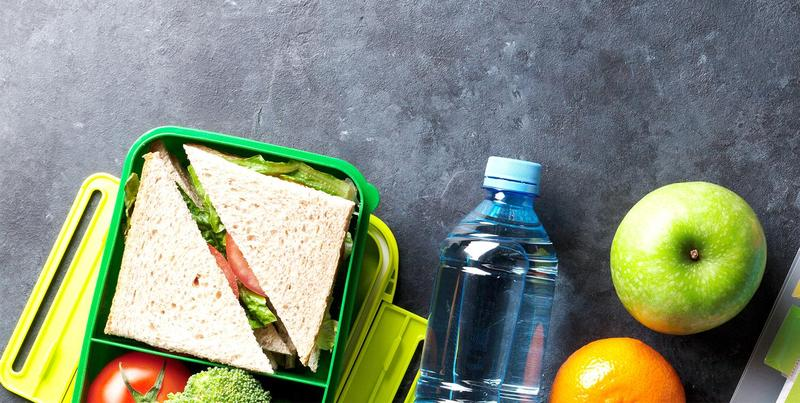 A sandwich in a container, a bottle of water, and two pieces of fruit on a table