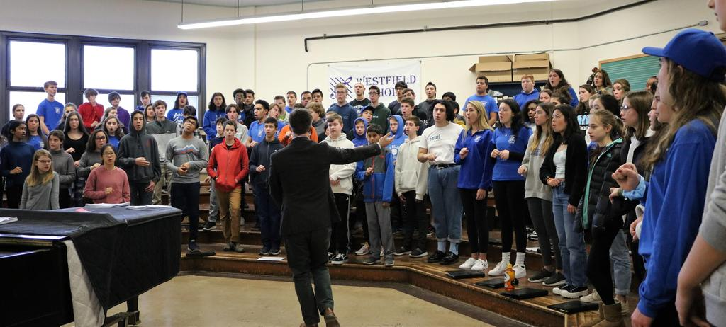 Photo of WHS chorus director working with high school and intermediate school student vocalists during District Music Day.