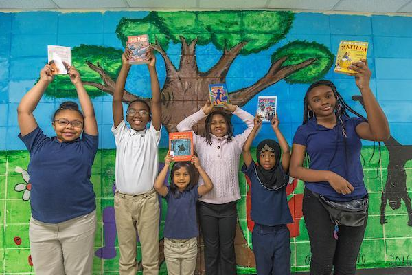Students with books in front of mural