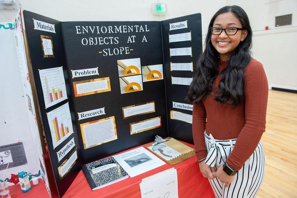 A student stands next to her project called Environmental Objects at a Slope
