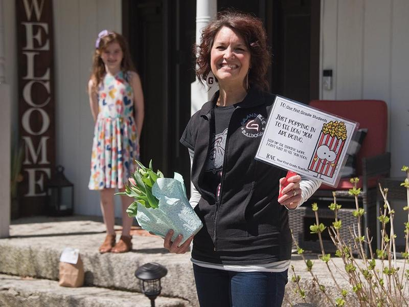 South teacher with tulips and a sign near a girl on a porch