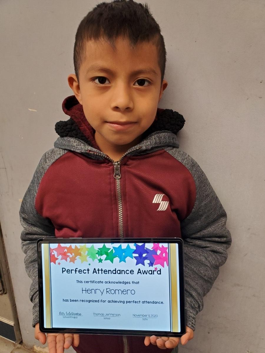 Henry Romero holding perfect attendance certificate
