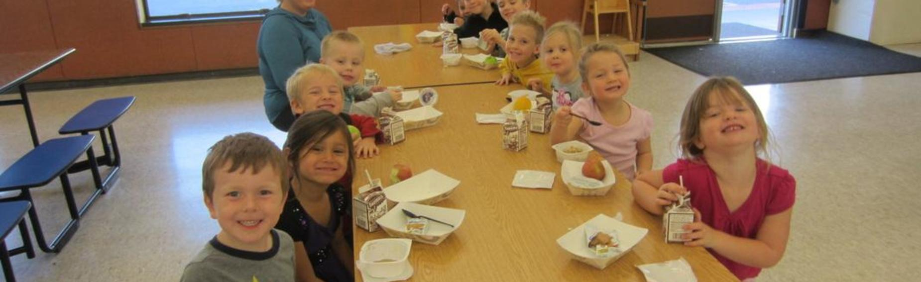 Children smiling while eating lunch at a cafeteria table.
