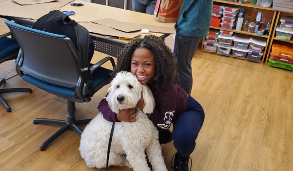 Student take a break to hug Lucy our therapy dog.