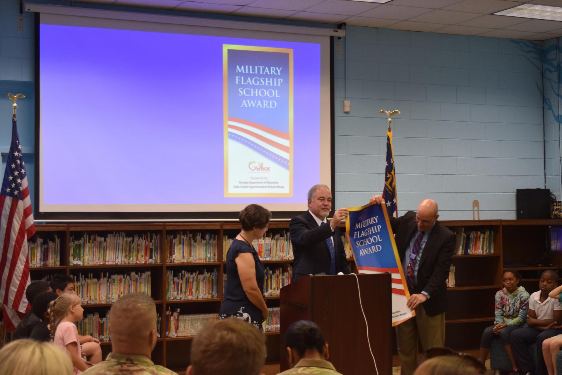 State Superintendent Richard Woods unfurls Military Flagship Banner award