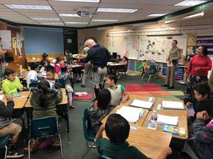 California Highway Patrol Officer reading to a group of students, image 2