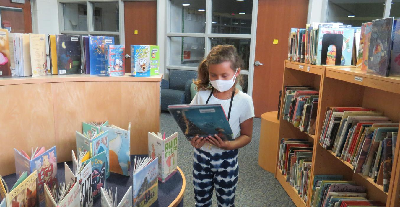 A Lee student picks out a book to read in the library.