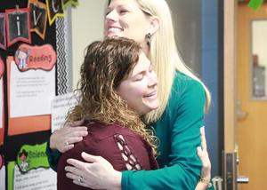 Foundation Board president hugs teacher grant recipient