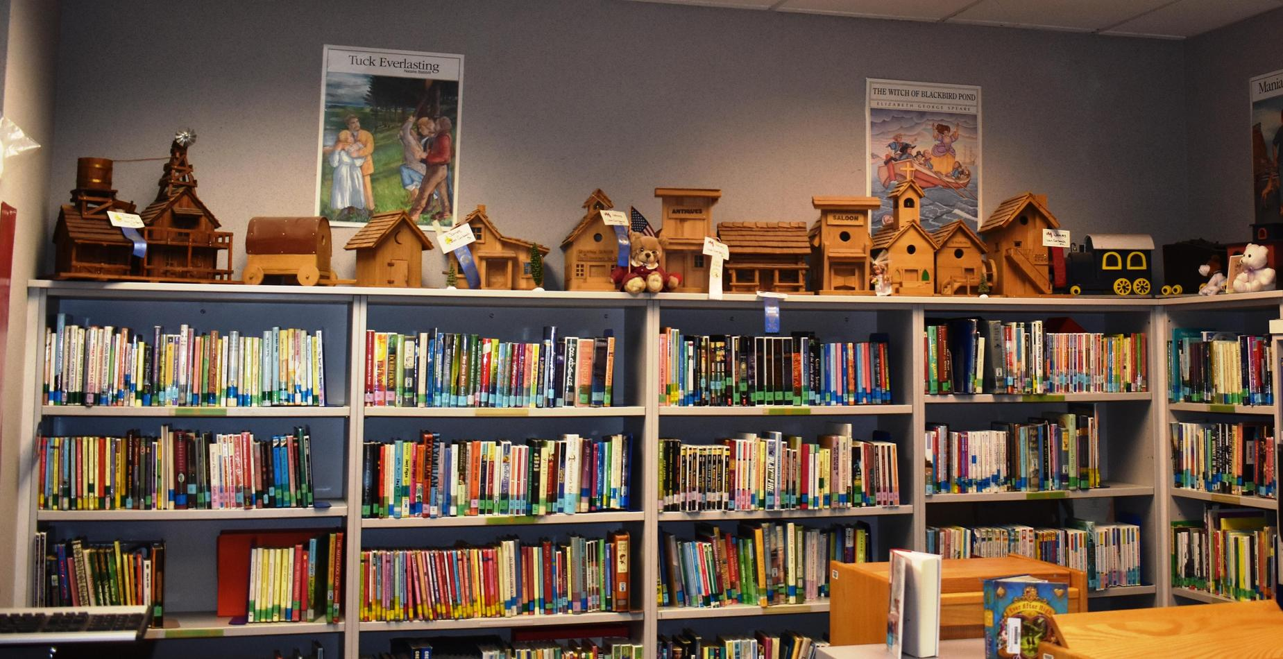 The library book shelves with hand made bird houses lining the top.  They were created by Mrs. DeBock's father.