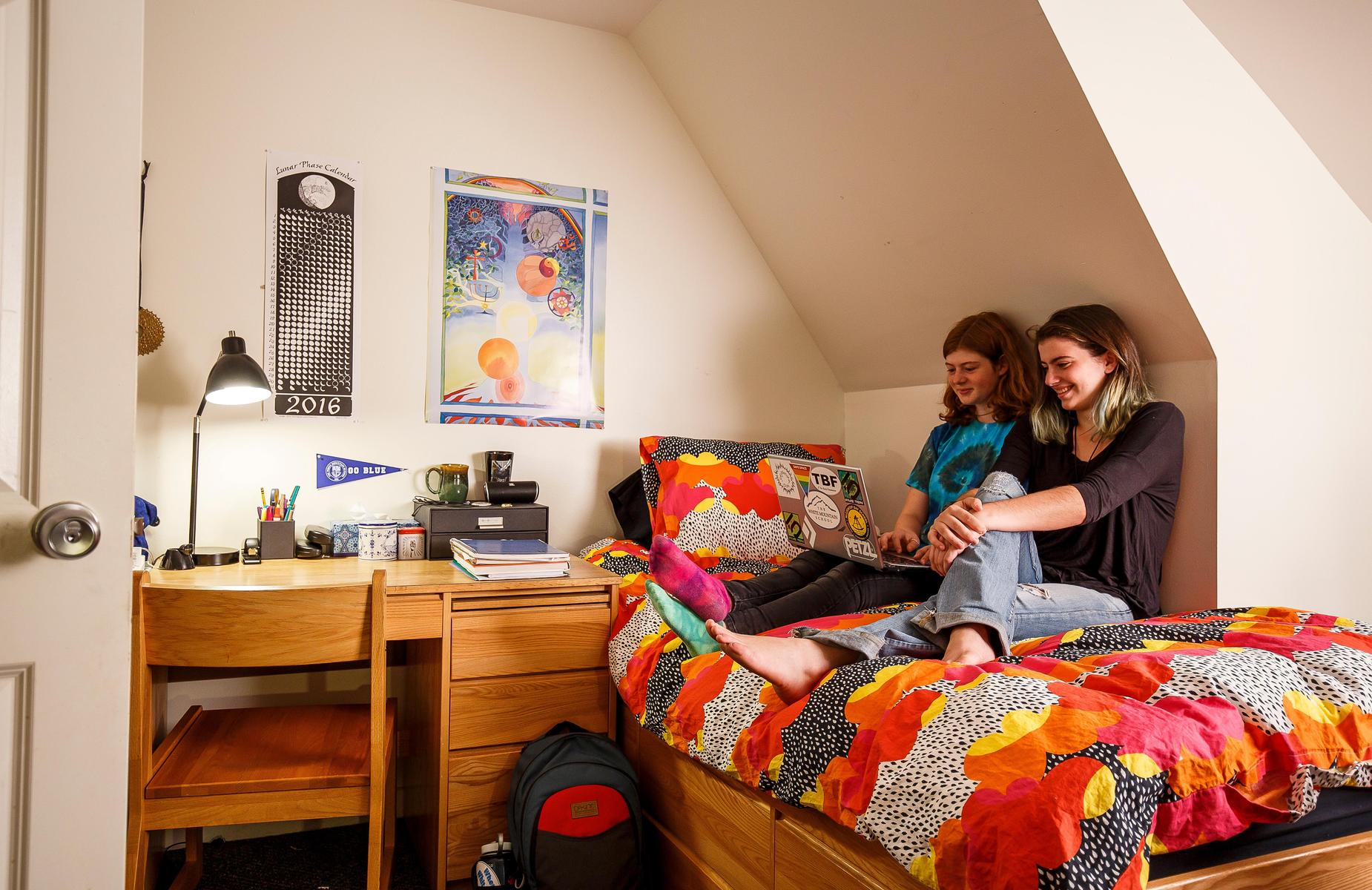 Two students watching a movie in a dorm room.