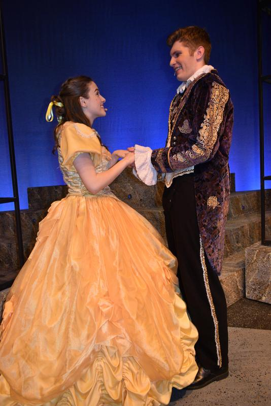 teen girl in yellow ballgown holding hands and looking into the eyes of teen boy in suit