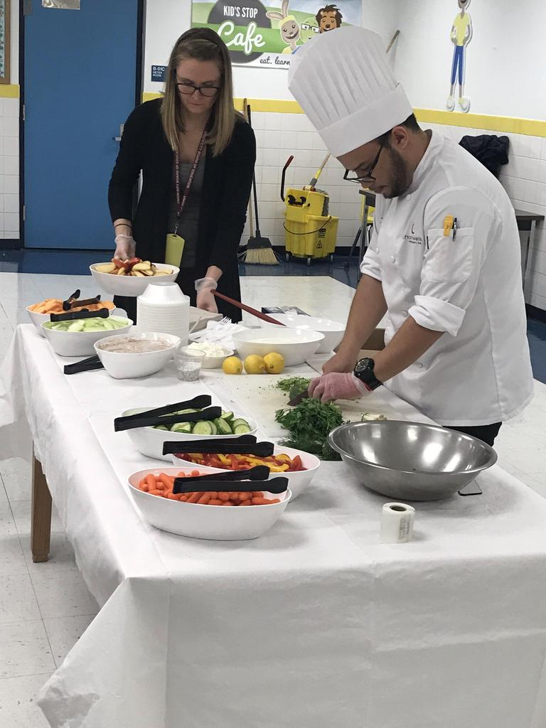 Chef Josh chopping up cilantro and Ms. Henderson moving plates around