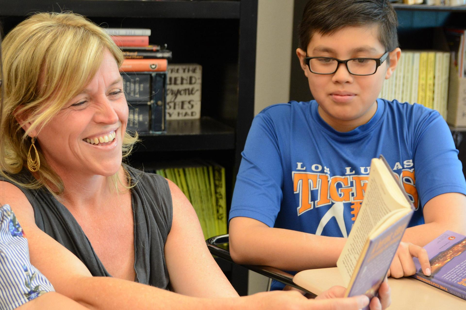 Teacher reading book with middle school student