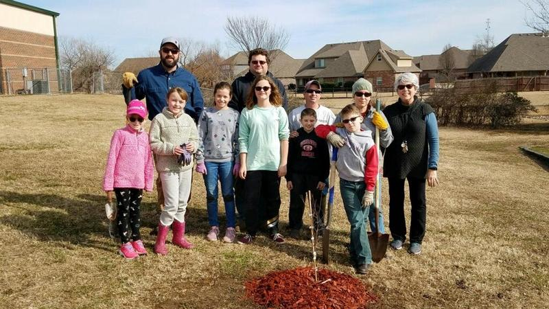 People planting trees with shovels