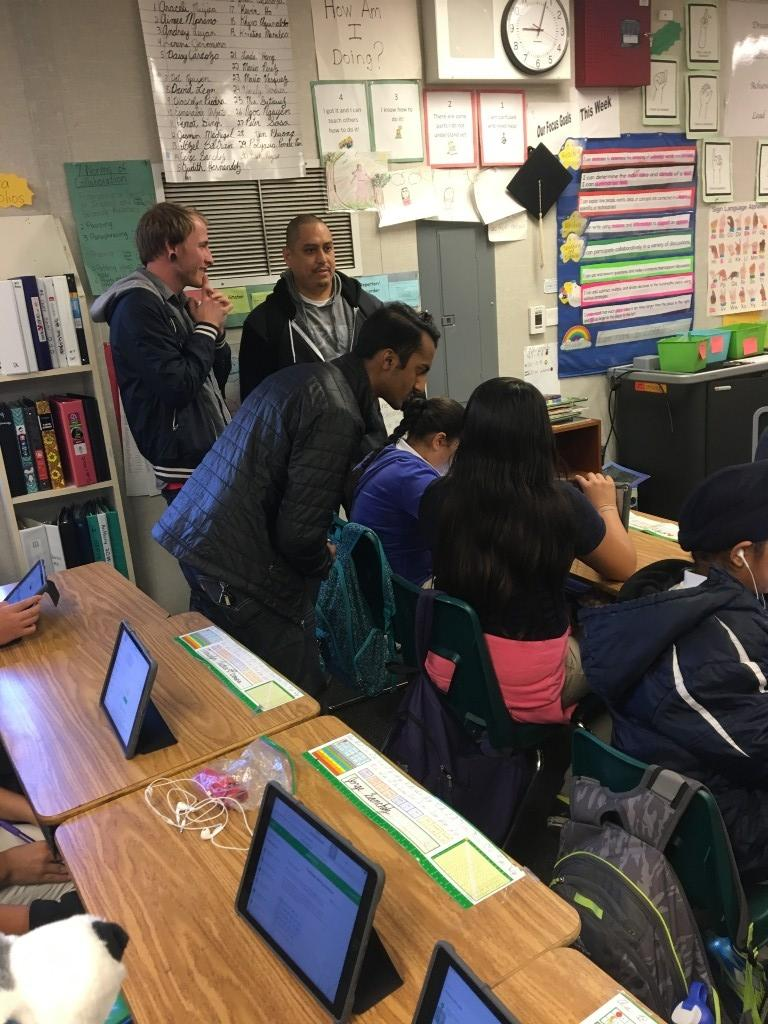 Apple employees assisting students on iPads