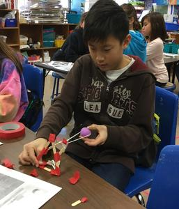 "Photo of:  Jefferson 5th grader Ethan Cha tests his catapult prototype during makerspace activities in early March.  ""Kids are encouraged to think outside the box and use the materials in the room in whatever creative ways they come up with,"" said art teacher Tracy Ciotti, who designed the activities."