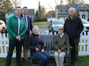 Members of the Juelis family, including sons Mark and Craig (left) and husband John, attend a dedication ceremony for a memorial bench in honor of veteran educator Mary Jo Juelis who passed away in 2017.  Pictured here members of the Juelis family standing near and sitting on the memorial bench.