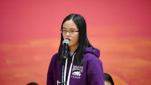 Photograph of student spelling a word at spelling bee.