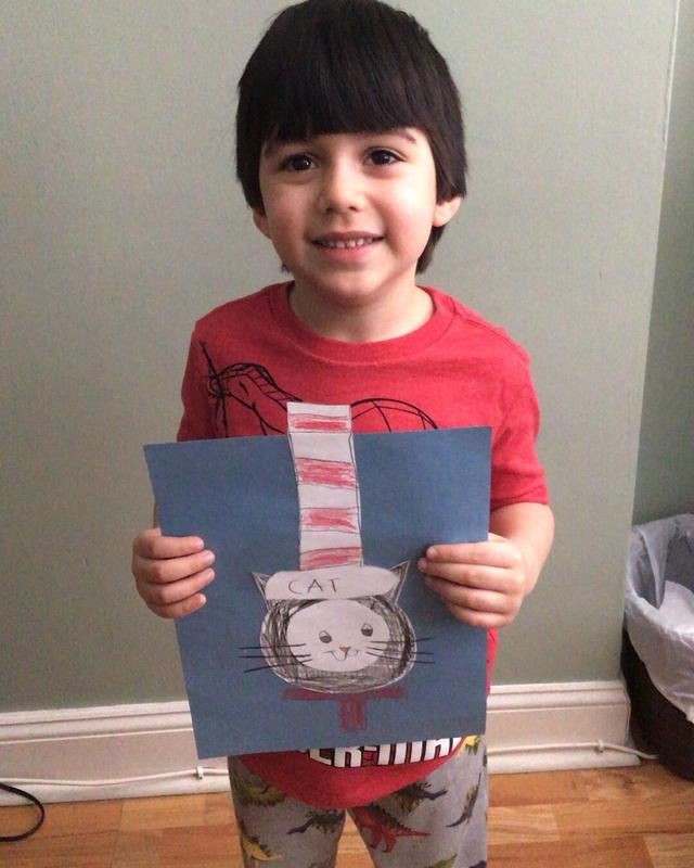 Boy holding Cat in the Hat drawing