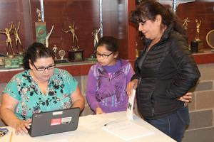 Staff member checking in a parent & child at family engagement event