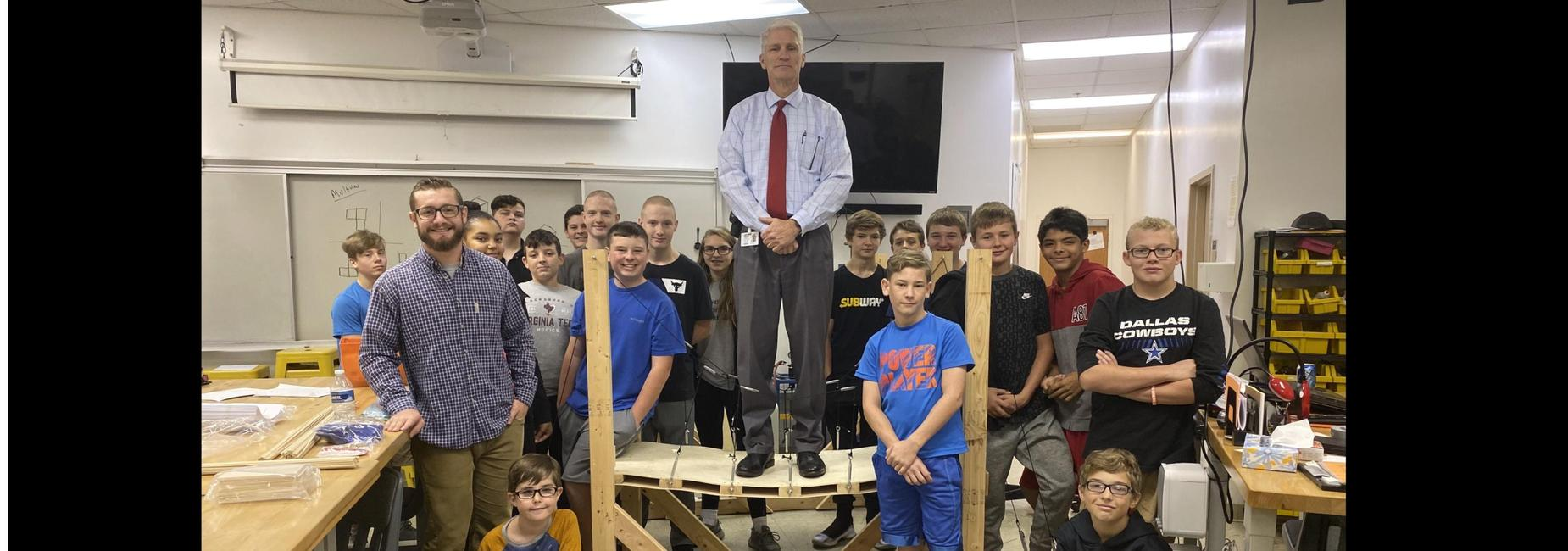 Mr. Blevins on a bridge built by Mr. Pierce's technology class.