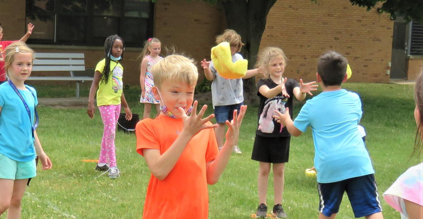 Lee students toss a wet sponge back and forth to fill a bucket.