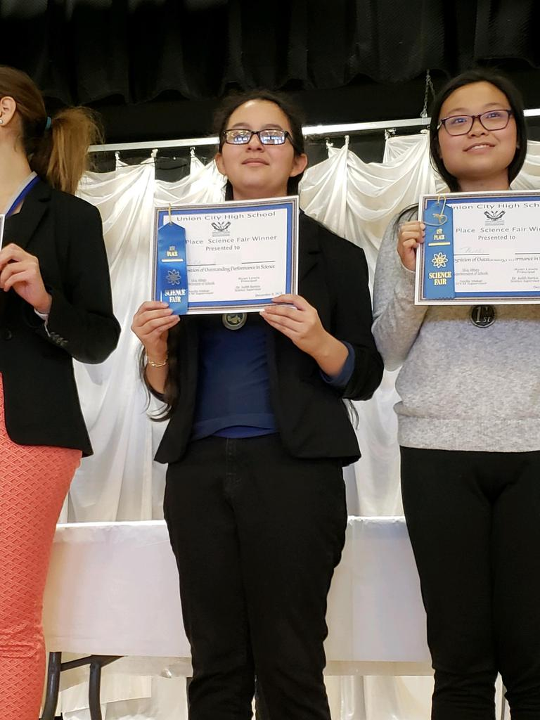 two uhms female students on stage with their certificates