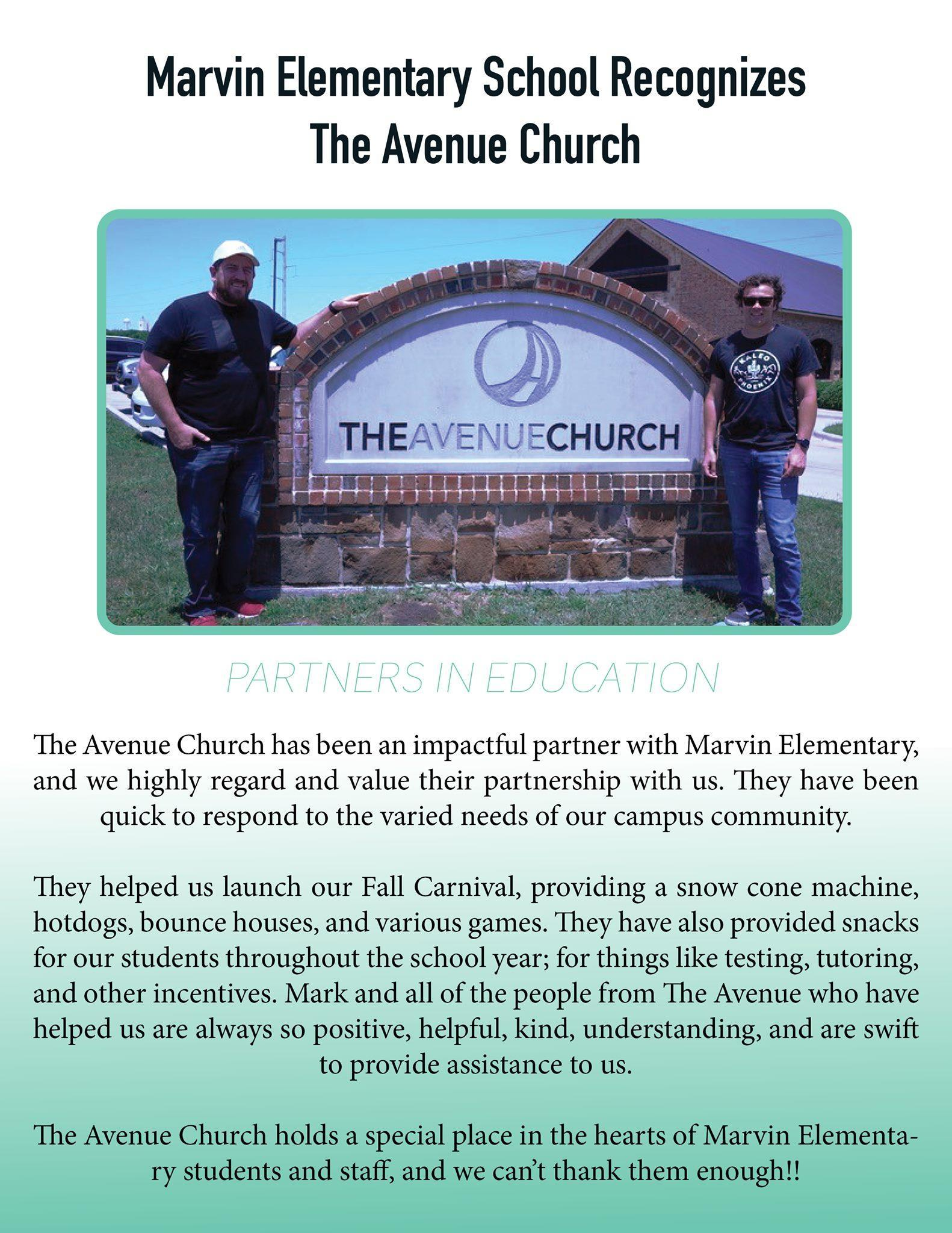 2 men standing by The Avenue Church sign