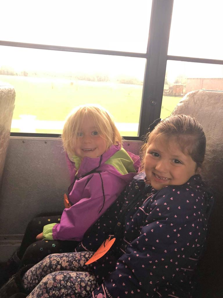 two children sitting on bus, smiling
