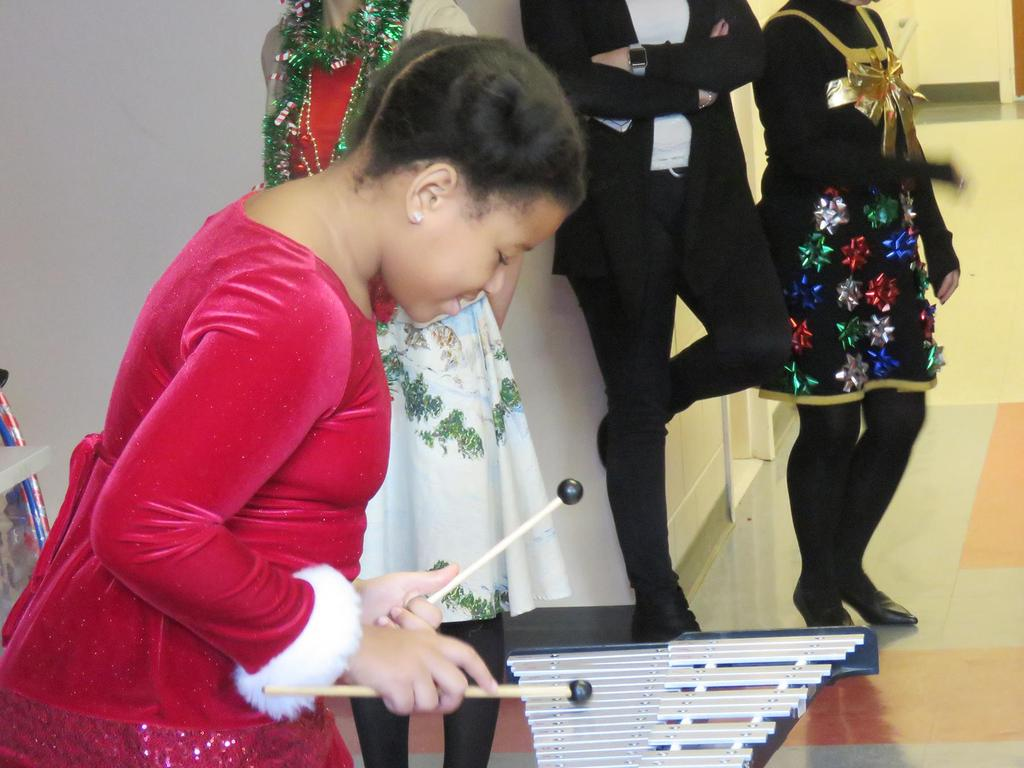 A girl plays jingle bells on a percussion instrument