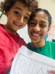 mom with child holding her activity sheet