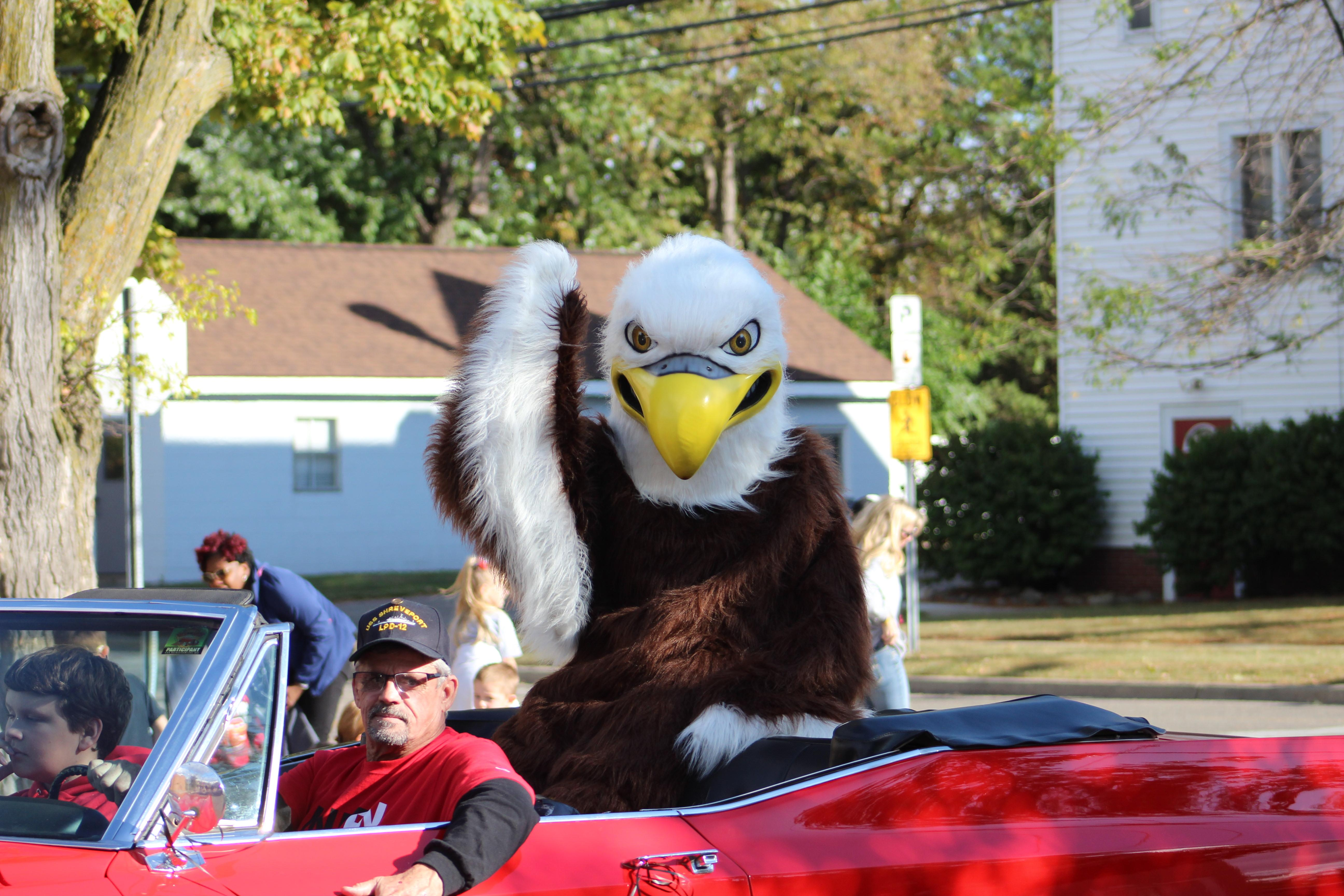 Eagle mascot riding in a convertible car during a parade