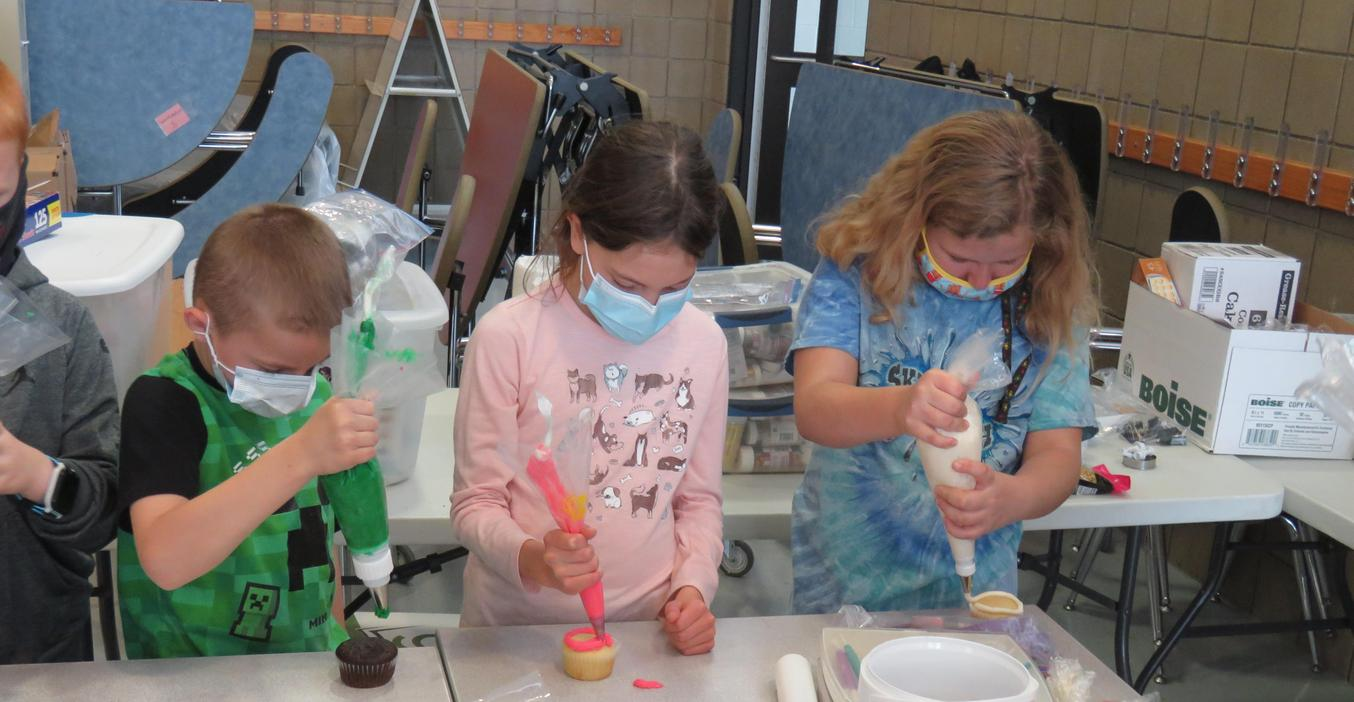 Lee students use frosting piping bags to frost their cupcakes.