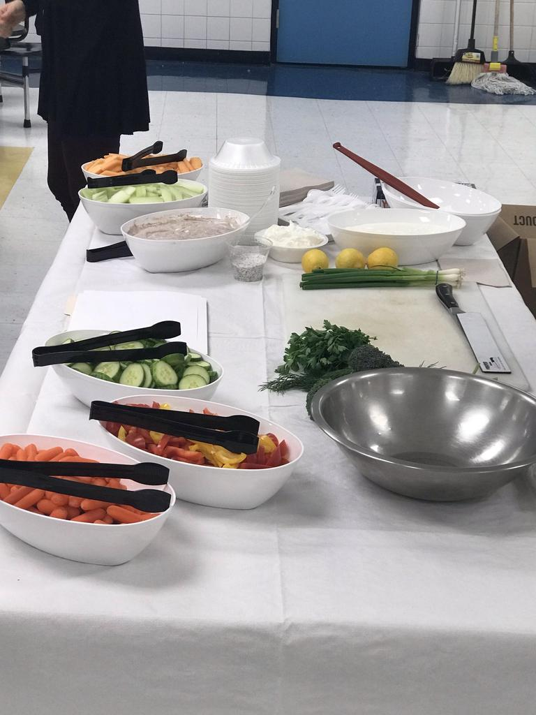 a table set up with carrots, peppers, cucumber mint and empty mixing bowl, celery, yogurt scallions