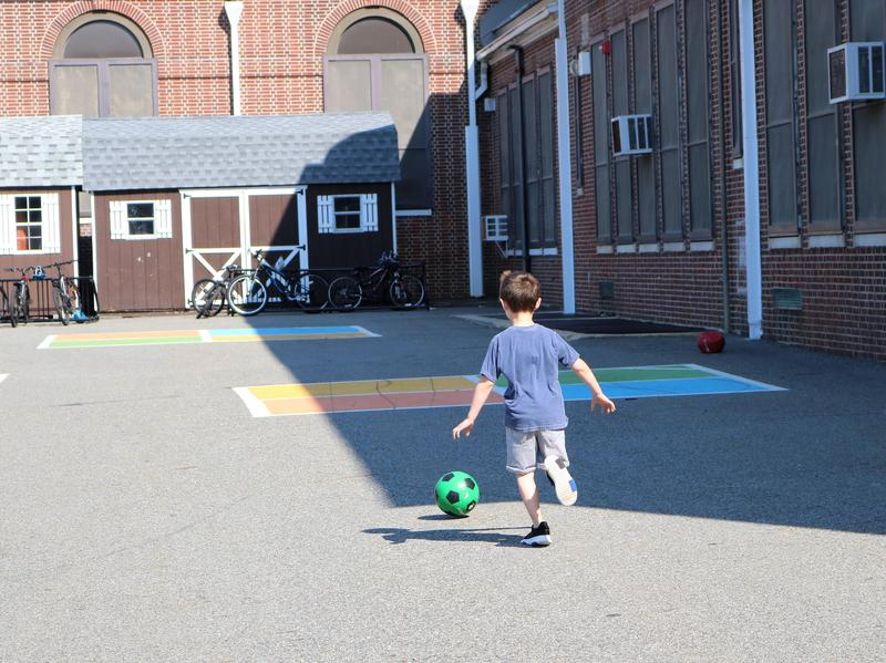 "A first grader enjoys a sunny day on the blacktop at Wilson School during ""Peaceful Playground,"" a fun and engaging course on conflict resolution that is part of the Extended School Year Program."